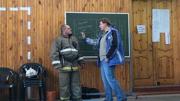 Отец троих детей, погибших при пожаре, разговаривает с одним из руководителей спасательной операции